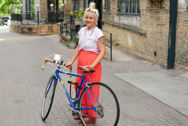women-i-work-with-carly-coughlin-pink-shirt-orange-pants-bike