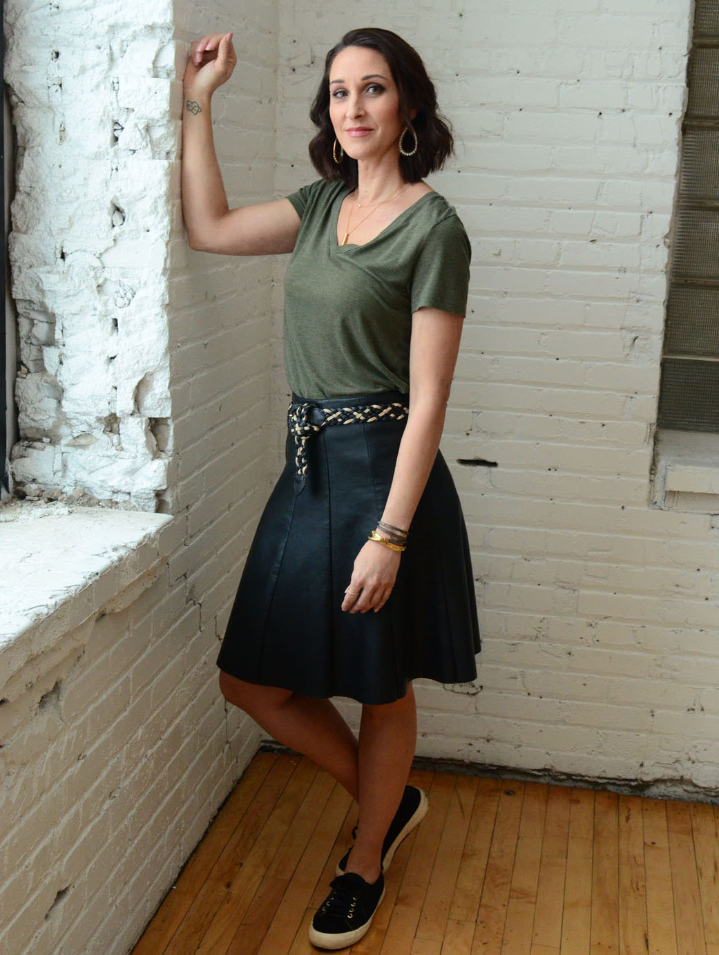 women-i-work-with-kristin-schroeder-black-leather-skirt-olive-tee-sneakers